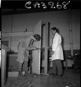 B.C. Vocational School; Carpentry Trades student building a door frame with an instructor assisti...