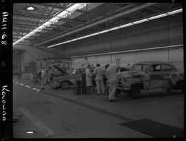 B.C. Vocational School image of an Automotive program instructor and students working on vehicles...