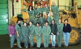 BCIT women in trades; heavy duty, students in uniforms standing in front of a bulldozer [1 of 9 p...
