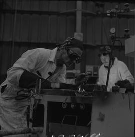 Welding, 1968; man wearing protective goggles welding ; man working in background