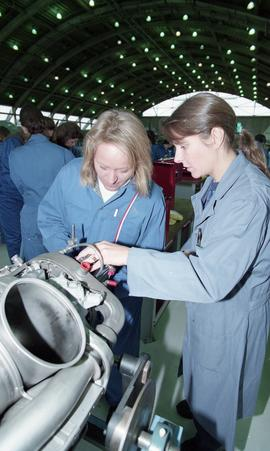 Two female students in uniforms inside a hangar using aviation tools