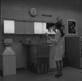 Medical radiography, 1968; woman in a lab coat holding an x-ray up to a light board