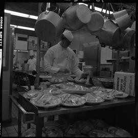 BC Vocational School Cook Training Course ; a student preparing salads ; trays of plated sandwich...