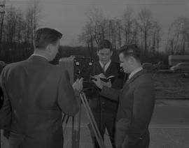 Survey, 1966; three men looking at a piece of equipment on a tripod - one man is wearing a headse...