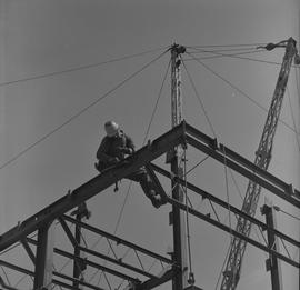 Structural steel, 1971; a worker sitting on the top beam of a structure tightening bolts on a beam