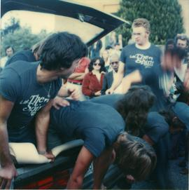 Student Rally 1984 ; a group of students laying in or climbing into the trunk of a car [1 of 2]