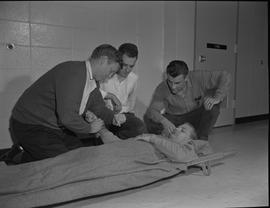 Industrial First Aid, Nanaimo; man taking the pulse of a man lying on a stretcher; two men observing