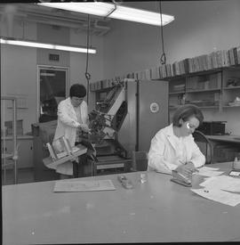 BCVS Graphic arts ; woman fixing a paper collator ; woman working at a desk