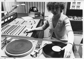 Broadcast Communication, 1980s; woman using turntables and control panel in the radio booth [1 of 2]
