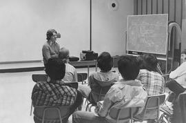 Broadcast Communications; instructor lecturing to students sitting in a classroom (white border c...