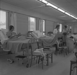 Practical nursing, Nanaimo, 1968; instructor and students talking ; patients sitting in beds in a...