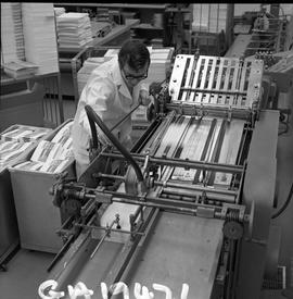 BCVS Graphic arts ; a man using a paper folding machine ; stacks of paper in background