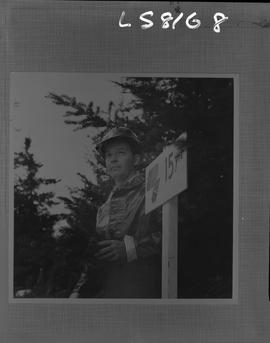 Logging, 1968; copy negative; picture of a man standing next to a '15 yrs' sign in a tree farm