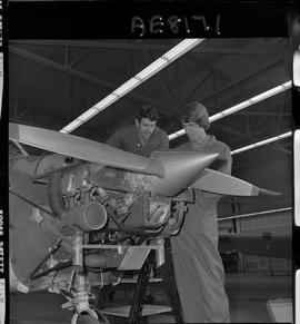 BC Vocational School; two Aeronautics students working on a small propeller aircraft engine insid...