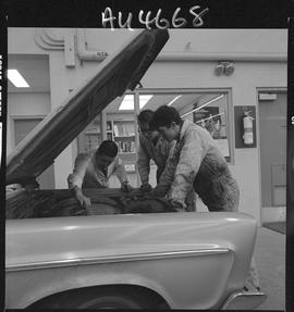 B.C. Vocational School image of an Instructor and Automotive Mechanics program students working o...