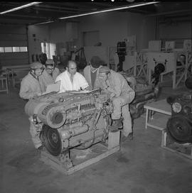 Marine engine repair, 1971; five men standing next to a large motor and looking at manuals [2 of 2]