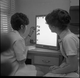 BC Vocational School Dental Assistant program ; two students examining x-rays of teeth ; photogra...