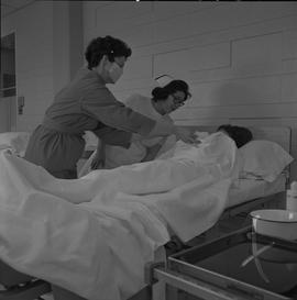 Practical nursing, Prince George, 1968; instructor and student wearing a face mask attending to a...