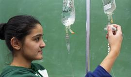 General Nursing, student checking intravenous drip bag [1 of 5 photographs]