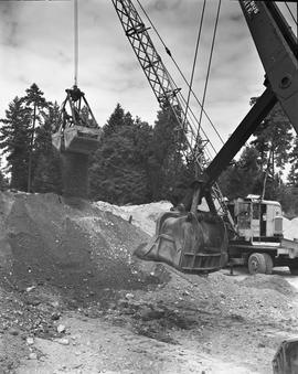Heavy duty equipment operator, Nanaimo ; excavator dumping dirt ; excavator in background