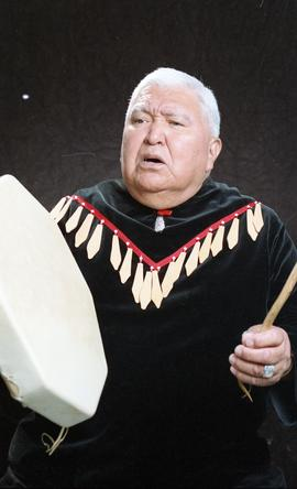 Bob George, First Nations elder, in First Nations garment playing an instrument [32 of 36 photogr...