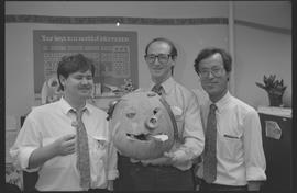 Staff posing with pumpkin carving of a pig (?) with a second place ribbon