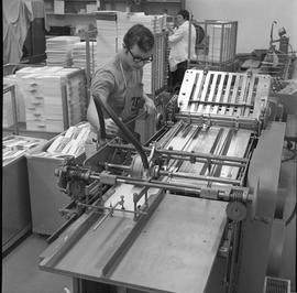 BCVS Graphic arts ; a man watching a paper folding machine ; stacks of paper in background [3 of 3]
