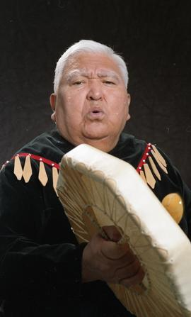 Bob George, First Nations elder, in First Nations garment playing an instrument [19 of 36 photogr...