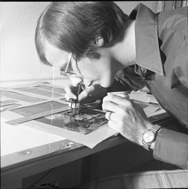 BCVS Graphic arts ; man using a loupe and painting an image on a poster