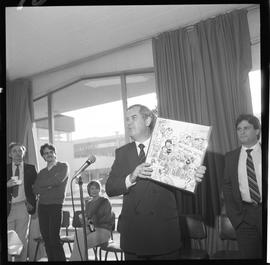 Merger of BCIT and PVI celebrations April 1986; Roy Murray holding up commemorative comic [1 of 3...