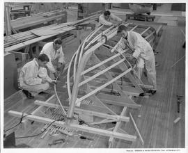 Four men building a boat frame in a workshop; Photo by the Division of Visual Education, Dept. of...