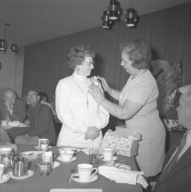 Roy Brown retirement party; a woman pinning a corsage onto Mrs. Brown's dress