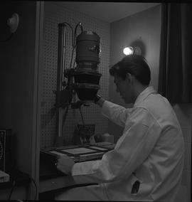 Medical radiography, 1968; man in a lab coat setting up a camera