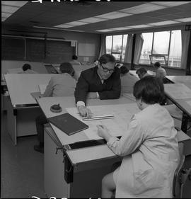 BC Vocational School drafting course ; instructor using a ruler to measure a student's diagram ; ...