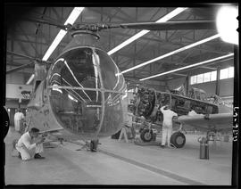 British Columbia Vocational School image of Aeronautics students working on a helicopter and an a...