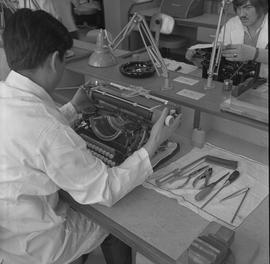 Office Machine Mechanic, 1968; man repairing a typewriter ; repairing tools on desk ; student wor...
