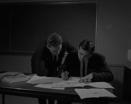 Business Technology; a man leaning over another man sitting at a desk, both reading a textbook