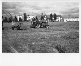 Agriculture; two men on a tractor baling hay