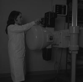 Medical radiography, 1968; woman in a lab coat putting film(?) in radiography equipment [1 of 2]
