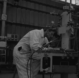 Welding, 1968; man looking at material on a workstation in front of him, welding torch resting on...