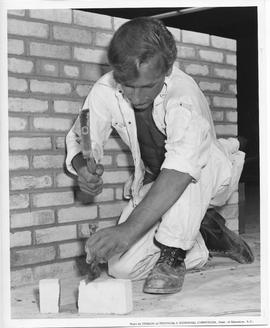 Bricklaying; student cutting a brick; Photo by the Division of Technical & Vocational Curricu...