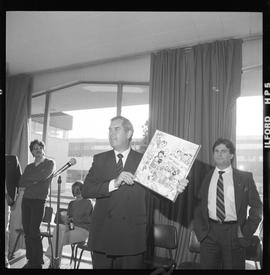 Merger of BCIT and PVI celebrations April 1986; Roy Murray holding up commemorative comic [2 of 3...