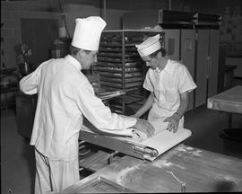 BC Vocational School Cook Training Course ; two students flattening dough using an industrial mac...