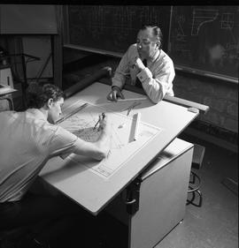 BC Vocational School drafting course ; student working on an electrical diagram while the instruc...