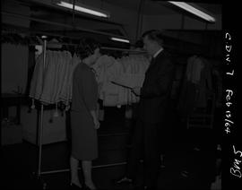 Business Management, 1964; a man and a woman standing in front of a clothing rack filled with wom...
