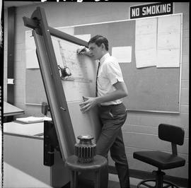 BC Vocational School drafting course ; student standing at an upright drafting desk and drawing ;...