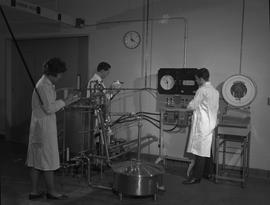 Food Processing Technology, 1966; three people in lab coats using food processing equipment - fem...