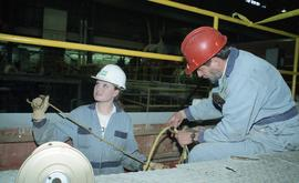 BCIT women in trades; BC Hydro, employee (?) and a student wearing uniforms and hard hats with BC...