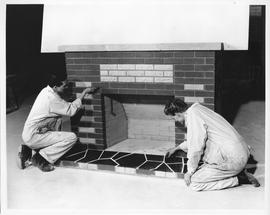 Bricklaying; two students cleaning the mortar on a brick fireplace in a workshop