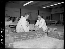 B.C. Vocational School image of a Bricklaying student in a shop building with bricks with an inst...